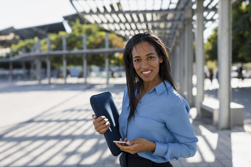 Businesswoman with smartphone, laptop bag - MAUF01834