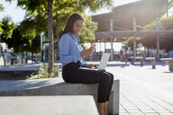 Businesswoman using laptop and smartphone - MAUF01837