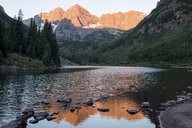 Scenic view of calm lake by trees and mountains against clear sky - CAVF58429