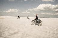 Friends riding motorbikes on desert road against sky - CAVF58438