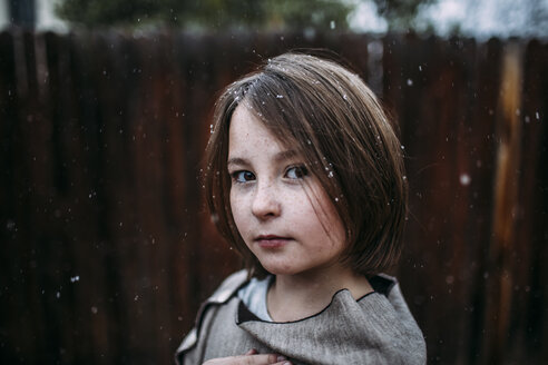 Portrait of confident girl at backyard during snowfall - CAVF58453