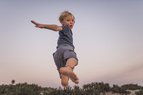 Low angle view of boy jumping on sand at beach against sky during sunset - CAVF58465