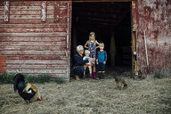 Grandchildren with grandmother looking at chickens at barn - CAVF58492