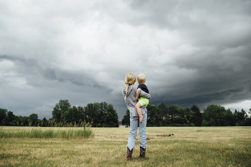 Rear view of sister carrying brother while standing on grassy field against cloudy sky - CAVF58498