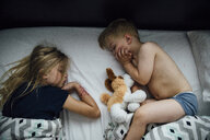 High angle view of siblings sleeping on bed at home - CAVF58501