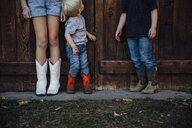 Siblings standing by wooden door - CAVF58504