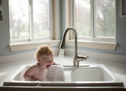 Cute shirtless baby boy sitting in kitchen sink against window at home - CAVF58516
