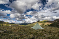 Tent on grassy field against cloudy sky - CAVF58537