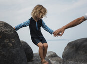Daughter holding hands of father while standing on rocks against sky - CAVF58549