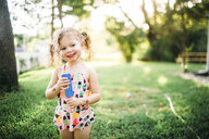 Smiling girl with popsicle standing on grassy field at backyard - CAVF58561