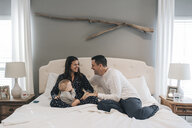 Happy family sitting on bed at home - CAVF58597