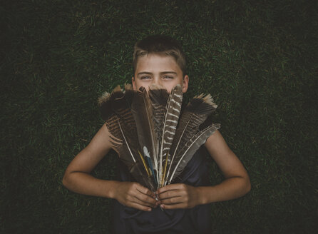 Portrait of boy holding feathers while standing against hedge at yard - CAVF58627