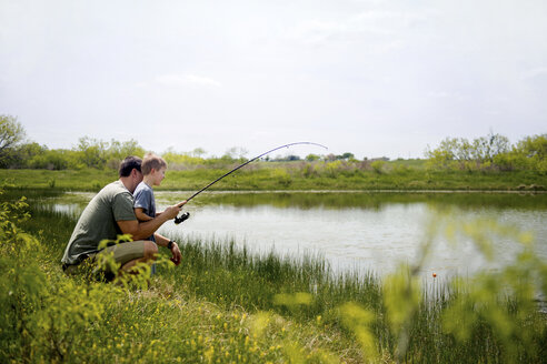 Side view of father and son fishing in pond against sky - CAVF58654