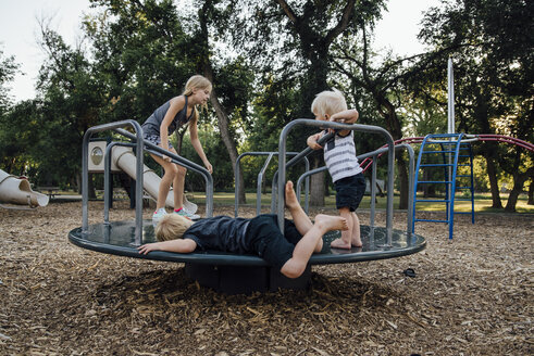 Siblings playing on carousel at playground - CAVF58672