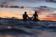 Silhouette friends in sea against cloudy sky during sunset - CAVF58687