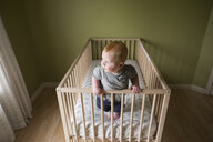 High angle view of baby boy standing in crib at home - CAVF58693