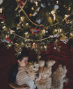 Overhead view of boy with dog lying by Christmas tree at home - CAVF58774