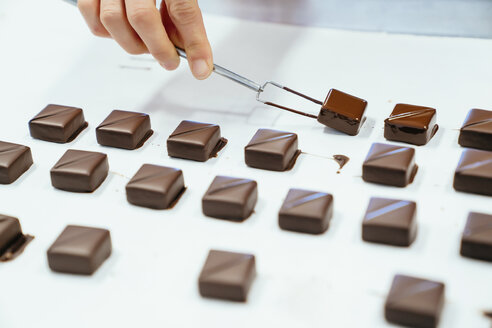 Cropped hand of chef holding chocolates with dipping fork in tray - CAVF58801