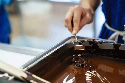Cropped hand of female chef dipping chocolate in fondue at factory - CAVF58804