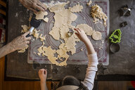 Overhead view of granddaughter helping grandmother in making Christmas cookies on table at home - CAVF58828