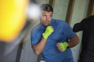 Midsection of coach boxing with athlete in gym - CAVF58834