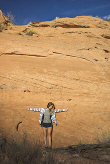 Full length of woman with arms outstretched standing against rock formations - CAVF58873