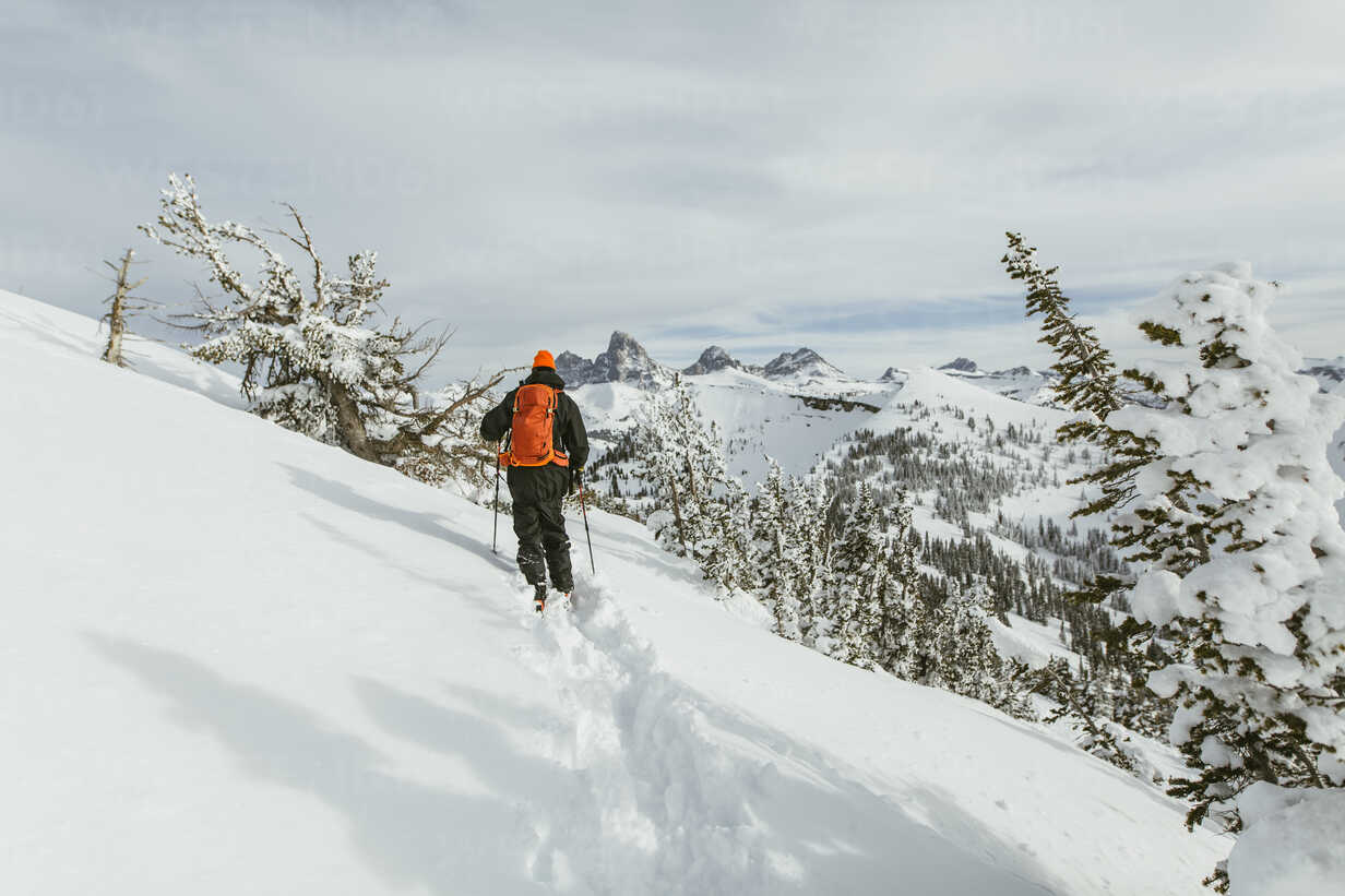 Rear view of hiker with backpack using ski poles while walking on snowcapped mountain - CAVF58876 - Cavan Images/Westend61