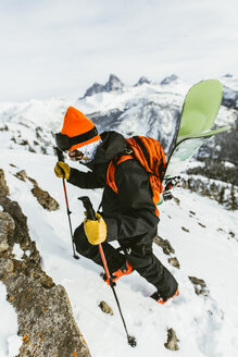 Hiker with backpack and ski poles climbing snowcapped mountain - CAVF58879