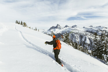 Hiker carrying ski on shoulder while climbing snowcapped mountain - CAVF58882