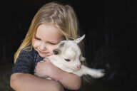 High angle view of girl embracing kid goat - CAVF58885