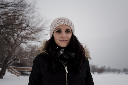 Smiling woman looking away while standing against sky during winter - CAVF58894