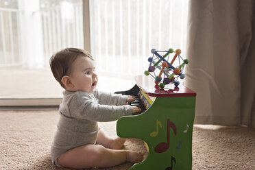 Side view of curious baby boy playing toy piano at home - CAVF58921