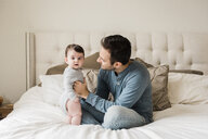 Portrait of cute son with father on bed at home - CAVF58927