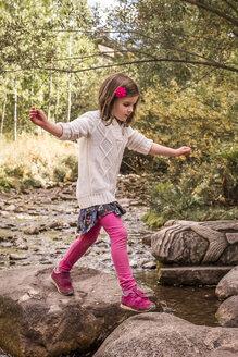 Side view of girl walking on rocks in forest - CAVF58981