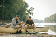 Friends with fishing rods talking while sitting on boat at lakeshore - CAVF59020