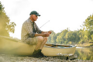 Senior man adjusting fishing tackle while sitting on boat at lakeshore against clear sky - CAVF59023