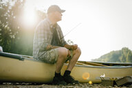 Thoughtful senior man sitting on boat at lakeshore against clear sky - CAVF59026