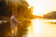 Senior man fishing while standing in lake against sky during sunset - CAVF59056