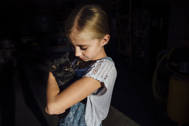 Girl holding cat while standing - CAVF59113