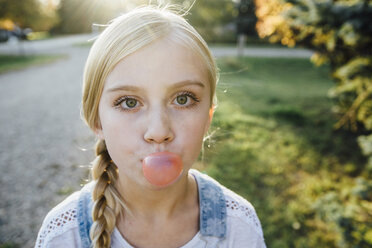 Portrait of girl blowing bubble gum while standing on field - CAVF59116