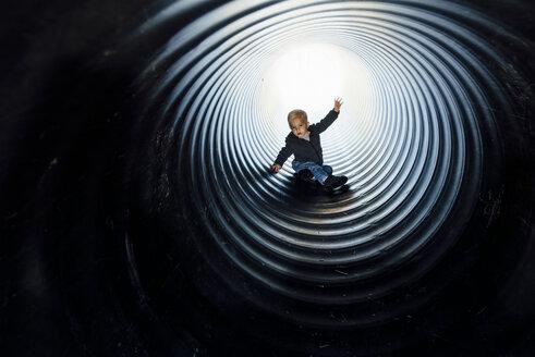Full length of boy sliding in slide at park - CAVF59128