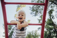 Low angle view of cheerful baby boy laughing while standing on monkey bars at park - CAVF59134