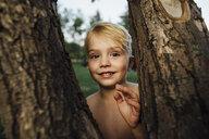 Portrait of boy standing by tree trunks - CAVF59158