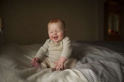 Cheerful baby boy with eyes closed sitting on bed - CAVF59167