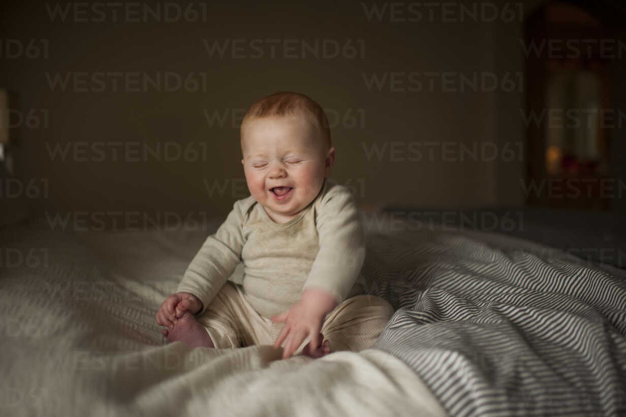Cheerful baby boy with eyes closed sitting on bed - CAVF59167 - Cavan Images/Westend61