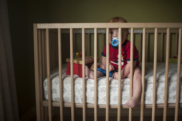Portrait of baby boy sucking pacifier while sitting in crib at home - CAVF59170