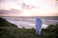 Denmark, Nordjuetland, Man wearing ice bear costume at the beach - REAF00470