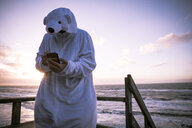 Denmark, Nordjuetland, Man wearing ice bear costume at the beach, using smartphone - REAF00473