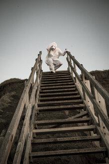 Man wearing ice bear costume on steps, despair - REAF00476