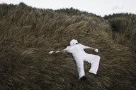 Denmark, Nordjuetland, Man wearing ice bear costume lying in grass - REAF00479